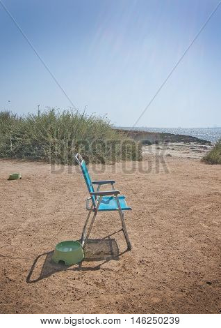 Blue beach chair and dog water bowls on a sunny day on July 30 2016 in Palma de Mallorca Balearic islands Spain.