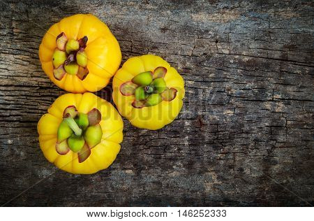 Top View.  Garcinia Cambogia Fresh Fruit On Wood Background.  Fruit For Good Health.