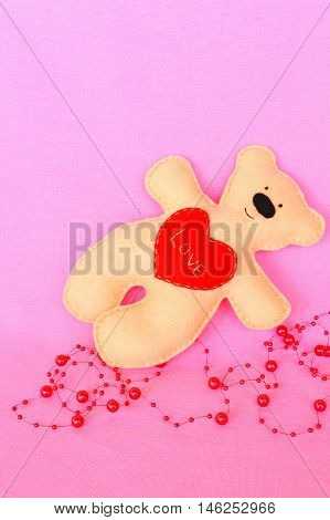 Handmade felt bear. Beige felt bear on pink background, hand-stitched toy, a craft out of felt