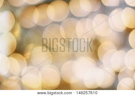 Abstract background of blurred golden holiday lights bokeh circles for Christmas background.