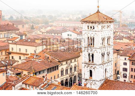 Aerial cityscape view on the old town of Lucca with San Michele basilicas tower at the foggy weather in Italy