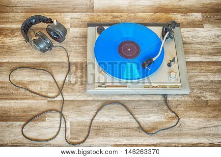 blue vinyl record spinning on the turntable, headphones plugged in, grunge wooden floor