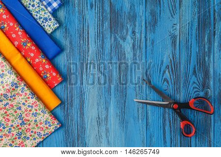 Sewing items on blue table, top view