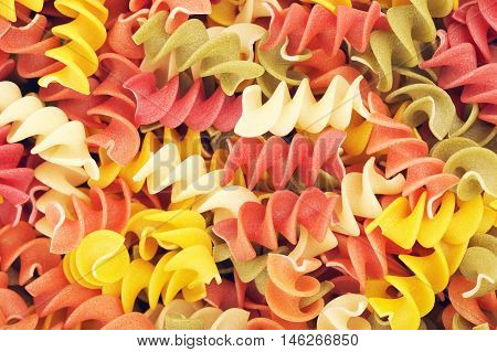 raw spiral pasta of different color, background