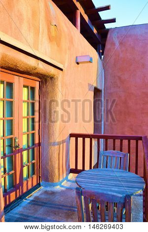 Southwestern style adobe building including Spanish colonial architectural design which has a balcony with rustic wooden outdoor furniture taken in Santa Fe, NM