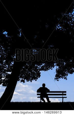 old man sitting alone on park bench under tree; a silhouette of resting retired senior;