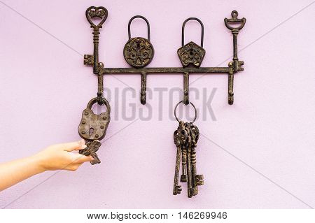 hand with brass antique skeleton keys hanging on pink wall