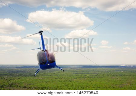 The aircraft - the small blue helicopter flight against the background of the cloudy sky.