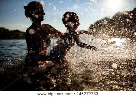 little kids play with sand on beach and jumping; female with child bathe in lake or river and making water drops;