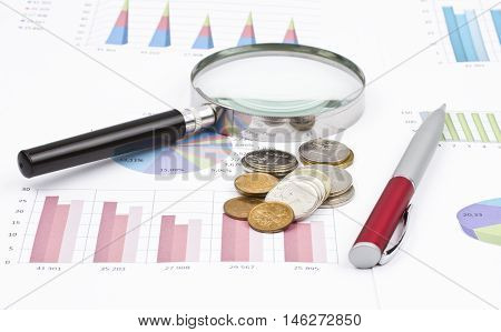 magnifier, pen and coins lie on the business charts