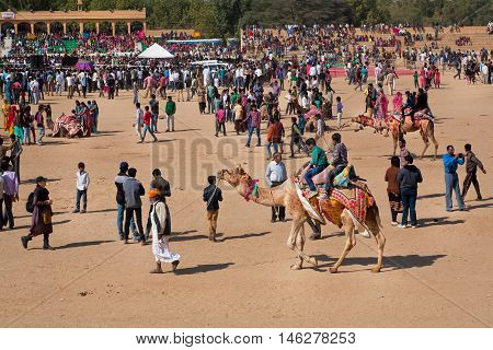 JAISALMER, INDIA - MAR 1, 2015: People in the crowd have fun with camels on the outdoor party during the rural Desert Festival on March 1, 2015. Every winter Jaisalmer takes the famous Desert Festival