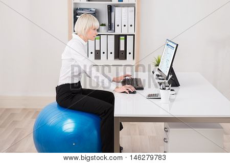 Young Businesswoman Sitting On Fitness Ball Looking At Gantt Chart On Computer
