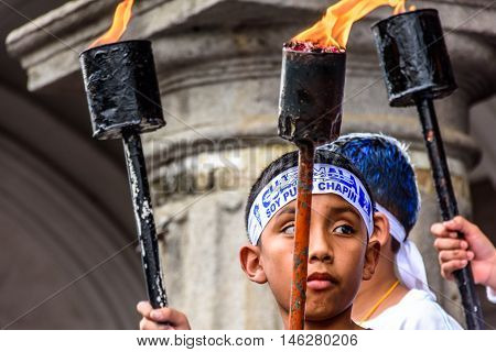 Antigua Guatemala - September 14 2015: Locals carry torches & wear patriotic headbands during Guatemalan Independence Day celebrations