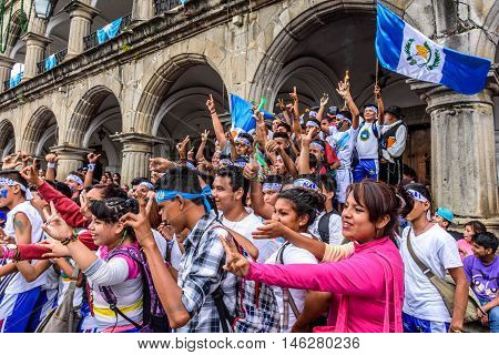 Antigua Guatemala - September 14 2015: Locals cheer in streets with Guatemalan flags & lit torches while blowing whistles & horns during Guatemalan Independence Day celebrations