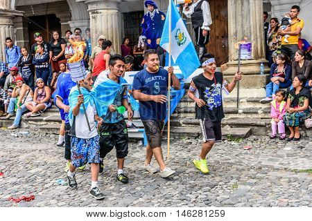 Antigua Guatemala - September 14 2015: Locals run in streets with Guatemalan flags & lit torches while blowing whistles during Guatemalan Independence Day celebrations