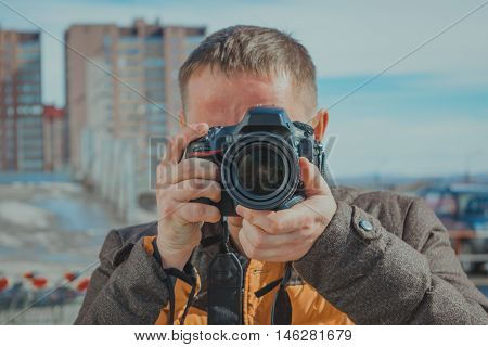 Young proffesional photographer close-up takes pictures outdoors.