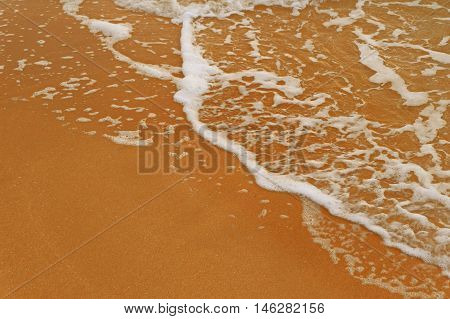 Sea beach sand with foamy wave a lot of space for text. Copyspace.