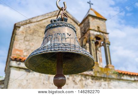 The close-up view of the small bell at the frontage of old church in Saro village Georgia.