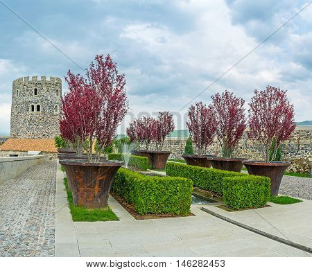 The colorful ornamental garden surrounded by massive ramparts and towers of Rabati Castle Akhaltsikhe Georgia.