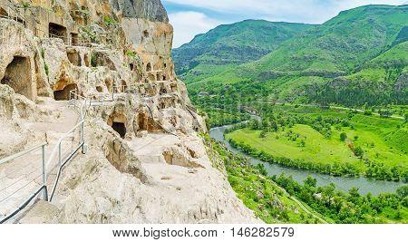 The narrow tourist way at the edge of precipice in Vardzia complex of carved in rock monastic caves Samtskhe-Javakheti Region Georgia.