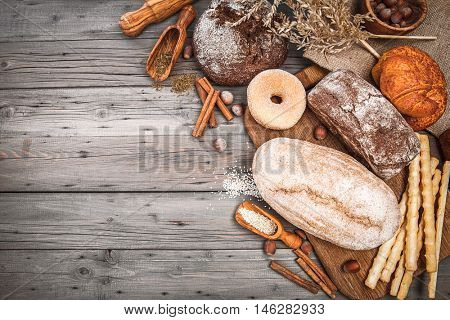 Fresh crispy breads baking of loaf and sweet donut croissant on old wooden plate in rustic style