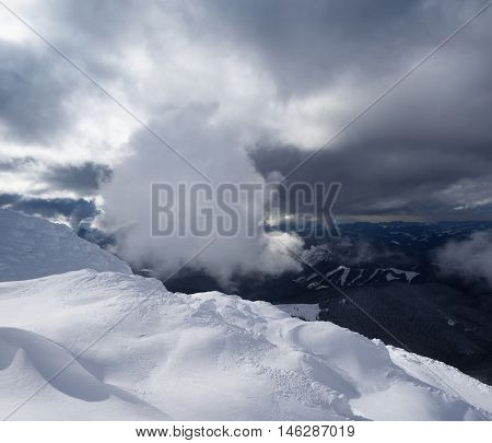 Winter landscape with a beautiful cloud. Snow drifts in the mountains