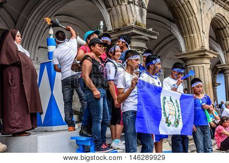 Antigua Guatemala - September 14 2015: Locals light torch & pose for photos with Guatemalan flag while nun watches outside city hall during Guatemalan Independence Day celebrations