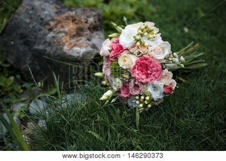 Beautiful wedding white and pink bouquet on a grass