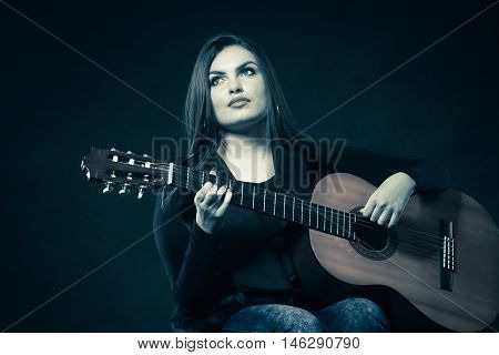 Music and people concept. Teen girl guitarist holds guitar studio shot on dark filtered photo
