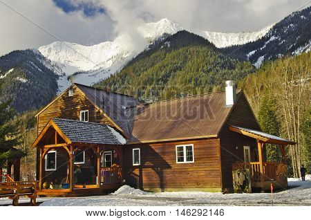 Wooden Cabin Among Snowy Mountains.