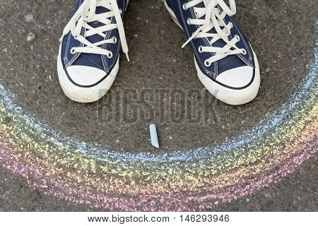 Feet in sneakers are on asphalt before drawn a rainbow