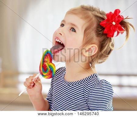 Cute little blonde girl with a red bow on her head, with pleasure licking colorful candy on a stick. Visible language which was painted in a candy color. Close-up.