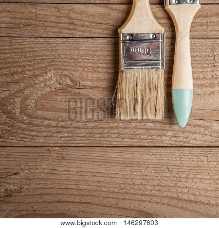 unused paint brushes on a wooden background