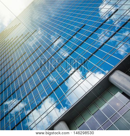 modern glass hi-rise building skyscraper over blue bright clear sky with sunlight