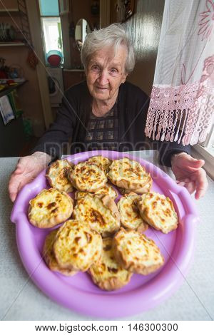 Elderly woman sitting at a table with a cakes - karelian pasty.