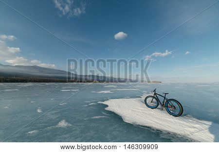 Fatbike (also called fat bike or fat-tire bike) - Cycling on large wheels. Bicycling is at sunset on the ice.