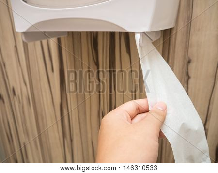 Pulling tissue paper in a public toilet