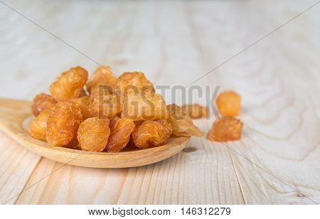 dried longan with wooden spoon and table background