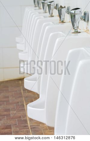 Urinals Men public toilet with selective focus