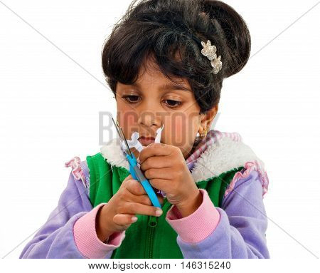 Child is cutting papper with blue scissor