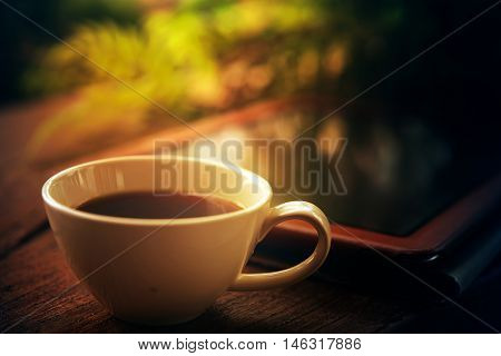 Tablet And White Coffee Cup On Wood