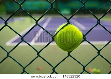 Tennis ball and steel cage in tennis court