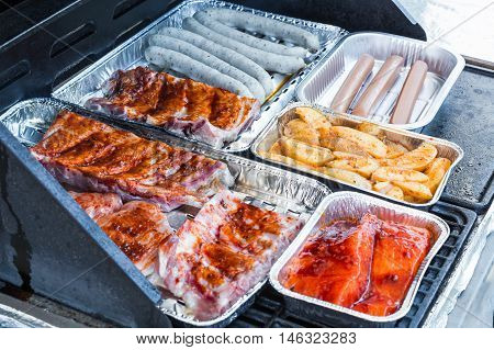Meat and grill sausages on a gas grill in aluminum dishes