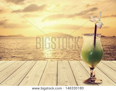 Tropical cocktail drinks on wooden desk, at tropical beach in summer sunset
