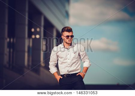 Fashion portrait of young sexy businessman handsome model man in casual cloth suit in glasses standing in the street behind blue sky