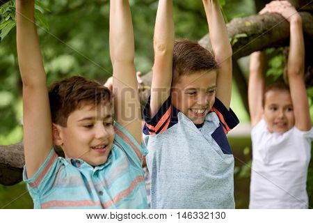 friendship, childhood, leisure and people concept - close up of happy kids or friends hanging on tree and having fun in summer park