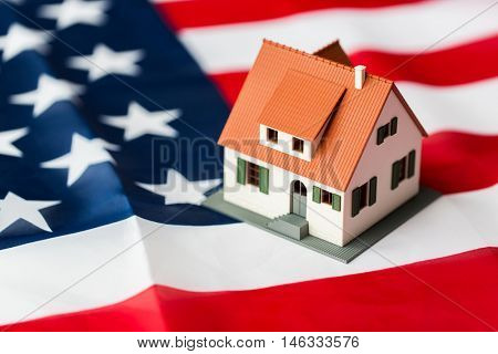 citizenship, residence, property, real estate and people concept - close up of living house model over american flag