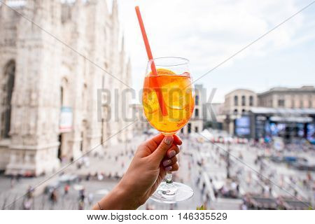 Holding a glass of spritz aperol drink on the main square with Duomo cathedral on the background in Milan city