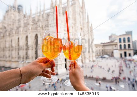 Clinking glasses of spritz aperol drink on the main square with Duomo cathedral on the background in Milan city