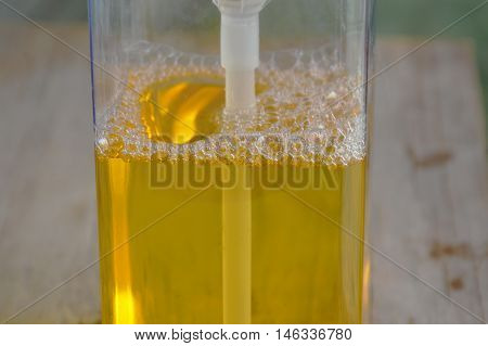 yellow dish washing soap bubble in square bottle